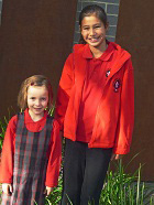 Some Girl's Winter Uniform Options: A winter pinafore with a long sleeved red polo shirt or black pants with a long sleeved polo shirt. The polo shirt is being worn with a red polar fleece jacket.